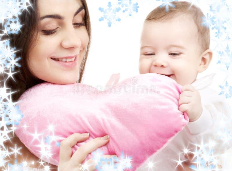 Schätzchen und Mutter mit heart-shaped Kissen lizenzfreie stockfotos