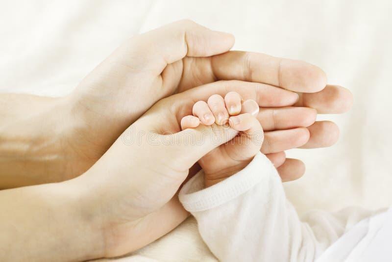 Schätzchenhand innerhalb der Muttergesellschafthände. Familienkonzept stockbild