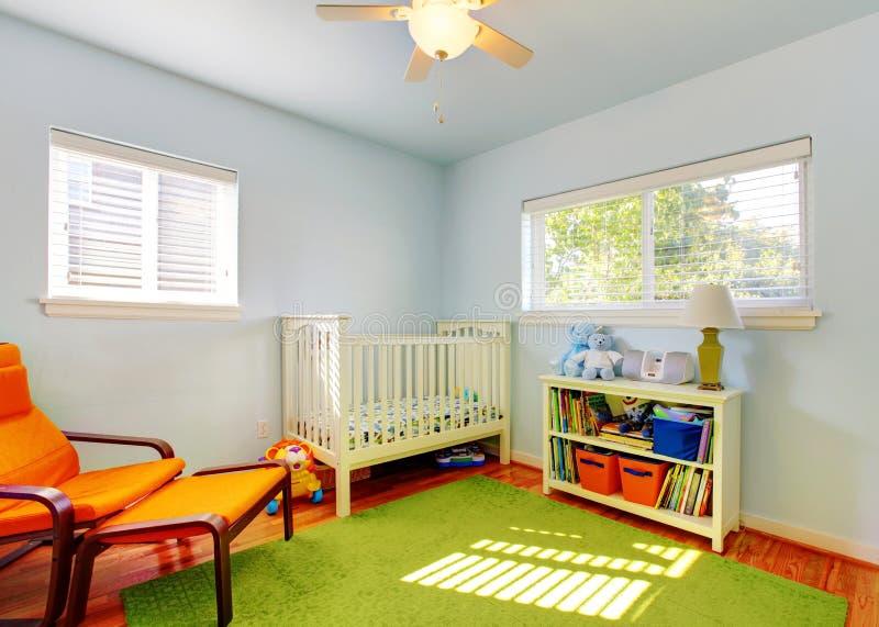 Schätzchenkindertagesstätten-Raumauslegung mit grüner Wolldecke, blauen Wänden und orange Stuhl. stockfotografie