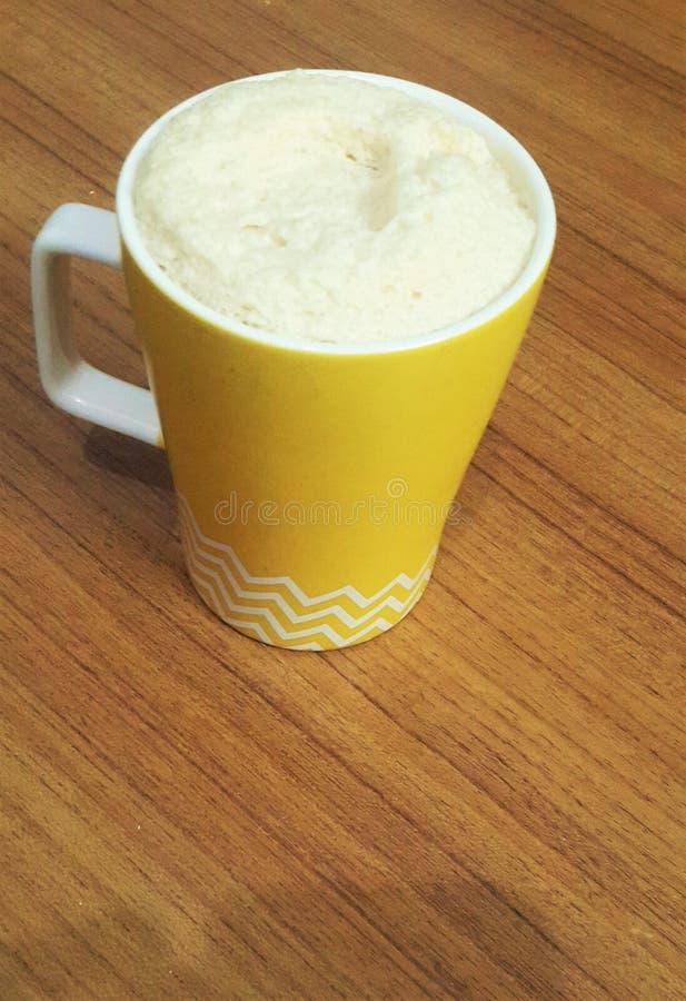 Schäumen der kalten Kaffeetasse auf Holztisch stockfotografie