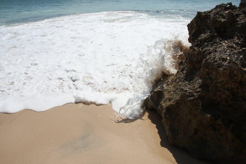 Schäumendes Wasser schlägt Felsen stockfotografie