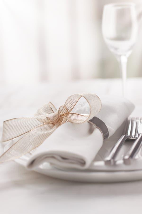 Schön elegante verzierte Tabelle für Feiertag - Hochzeit oder Valentinstag mit modernem Tischbesteck, Bogen, Glas, Kerze und Gesc stockfoto