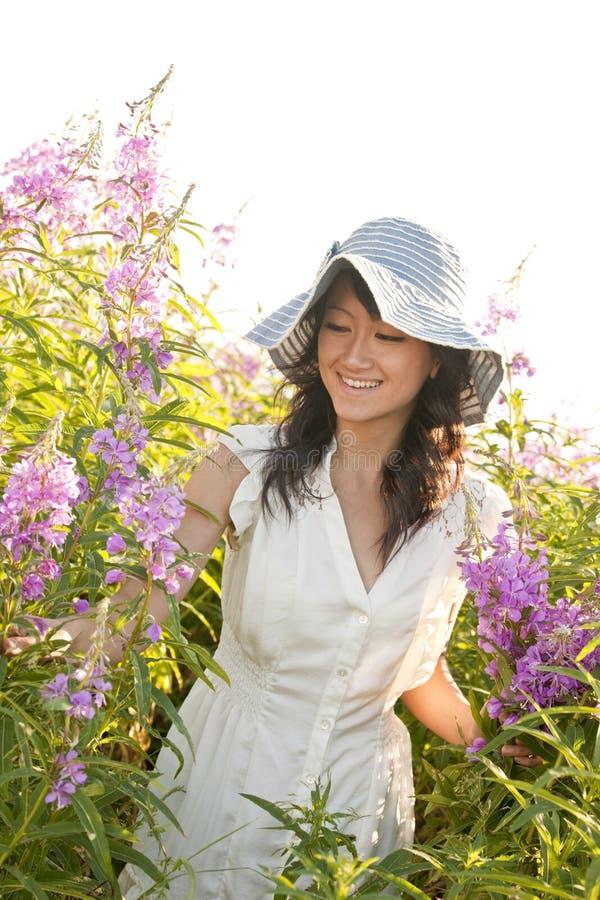 Schön, glücklich, gesund, lächelnd, junge Asiatin, die draußen Blumen im Sommer auswählt Sie trägt ein weibliches Kleid und eine  stockbild