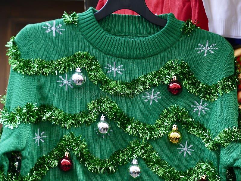 Schön oder hässlich: grüne Weihnachtsstrickjacke mit Dekorbällen stockbild