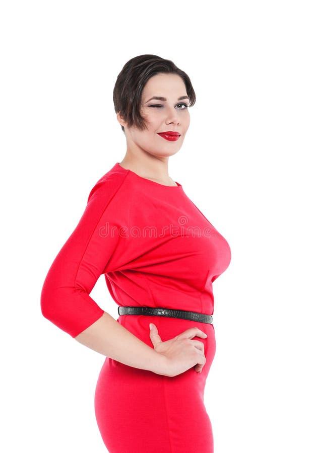 Schön plus Größenfrau im roten Kleiderblinzeln lokalisiert stockfotos
