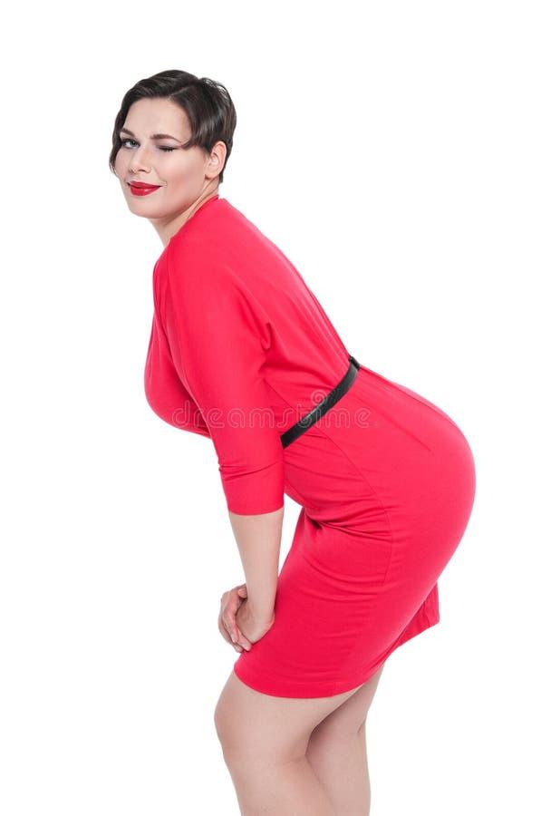 Schön plus Größenfrau im roten Kleiderblinzeln lokalisiert lizenzfreies stockfoto