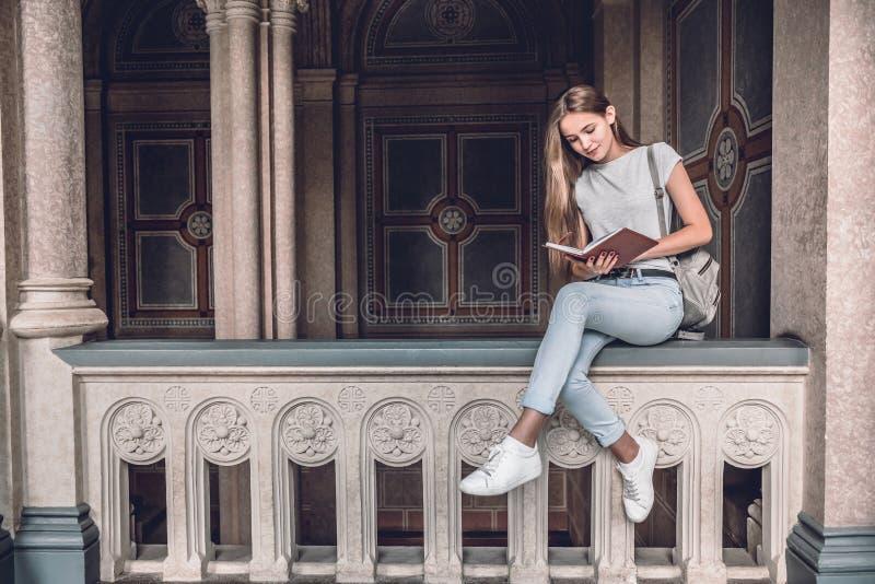 Schön und überzeugt Junge Studentin, die auf dem Geländer im Hochschulhallen- und -lesebuch sitzt lizenzfreies stockfoto