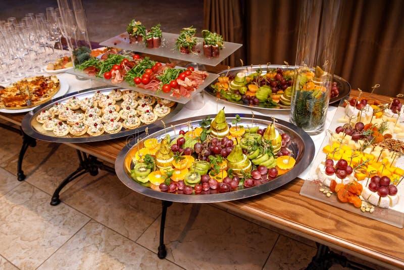 Schön verzierter versorgender Bankettisch mit verschiedenen Nahrungsmittelimbissen und -aperitifs auf Unternehmens stockfotografie