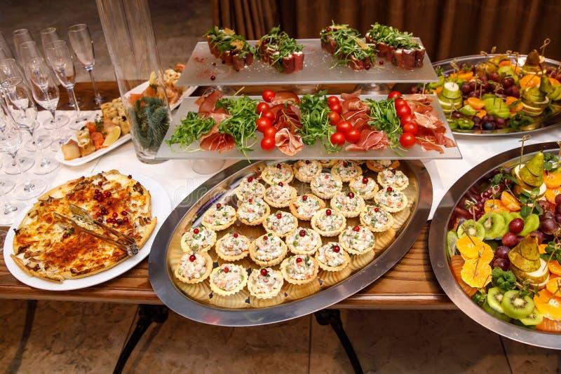 Schön verzierter versorgender Bankettisch mit verschiedenen Nahrungsmittelimbissen und -aperitifs auf Unternehmens lizenzfreies stockbild