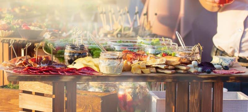 Schön verzierter versorgender Bankettisch mit verschiedenen Nahrungsmittelimbissen und -aperitifs mit Sandwich, auf Unternehmensw stockbilder