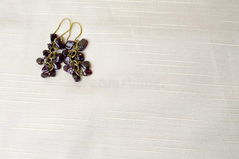 Schön, weiblich, Modeohrringe von den braunen dunklen Steinen, bernsteinfarbig auf einem Hintergrund des beige Gewebes lizenzfreie stockbilder
