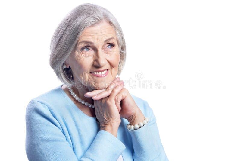 Schöne ältere Frau, die auf weißem Hintergrund aufwirft lizenzfreie stockbilder