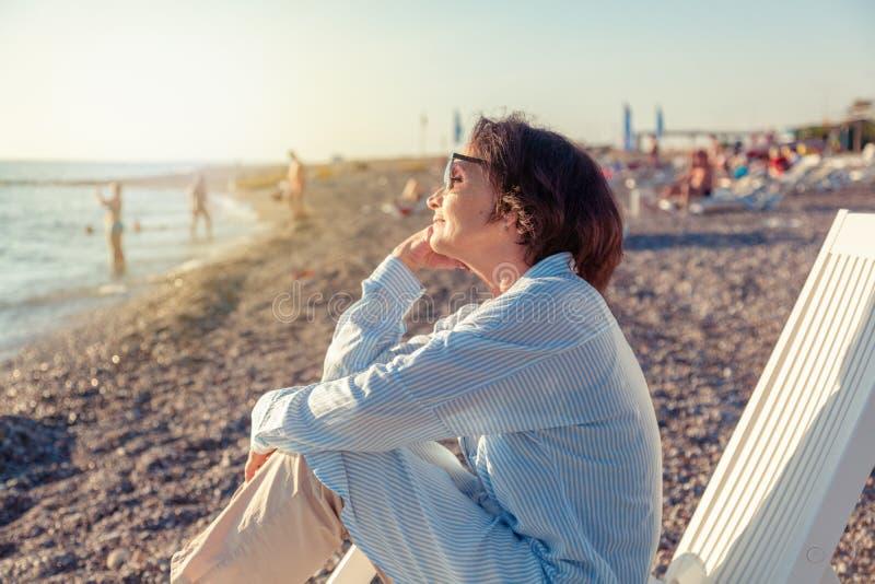 Schöne ältere Frau, die in einem deckchair auf dem Strand sitzt und stockfotografie