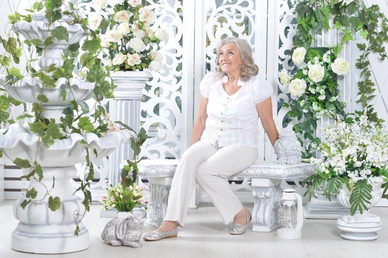 Schöne ältere Frau, die im hellen Raum verziert mit Weiß aufwirft stockfoto