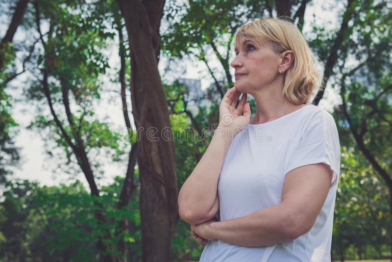 Schöne ältere Frau, die im Park denkt stockbild