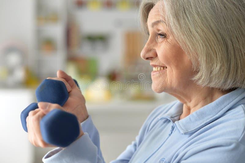 Schöne ältere Frau in einer Turnhalle mit Dummköpfen lizenzfreie stockfotos