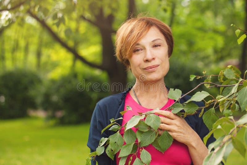 Schöne ältere Frau mit den grünen Blättern im Freien stockfoto