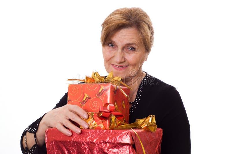 Schöne ältere Frau mit einem Geschenk lizenzfreie stockbilder