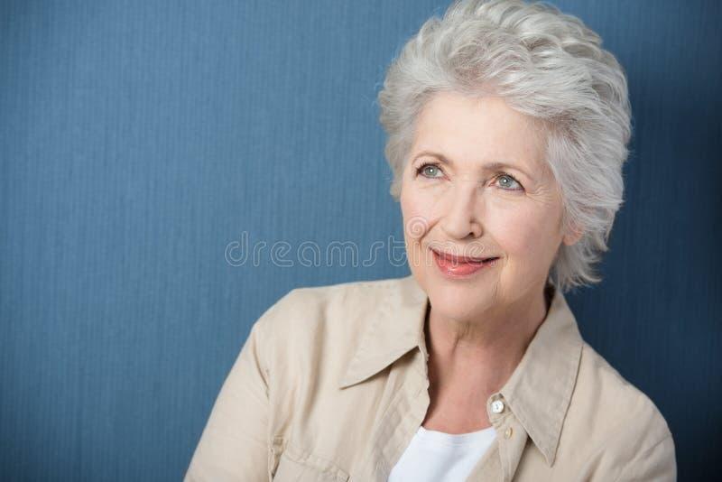 Schöne ältere träumende Frau stockfotografie