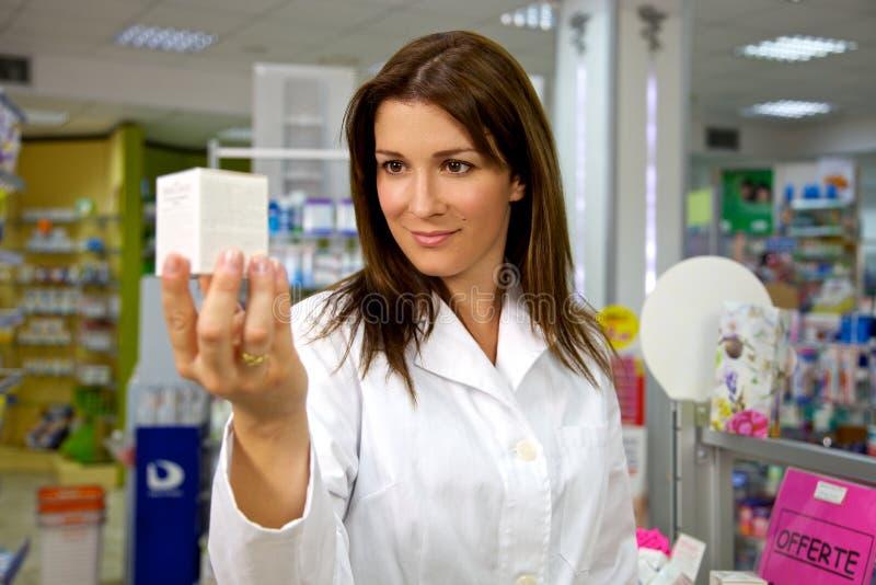 Schöne Ärztin in der Uniform, die Medizin beim Apothekenlächeln hält lizenzfreie stockfotografie