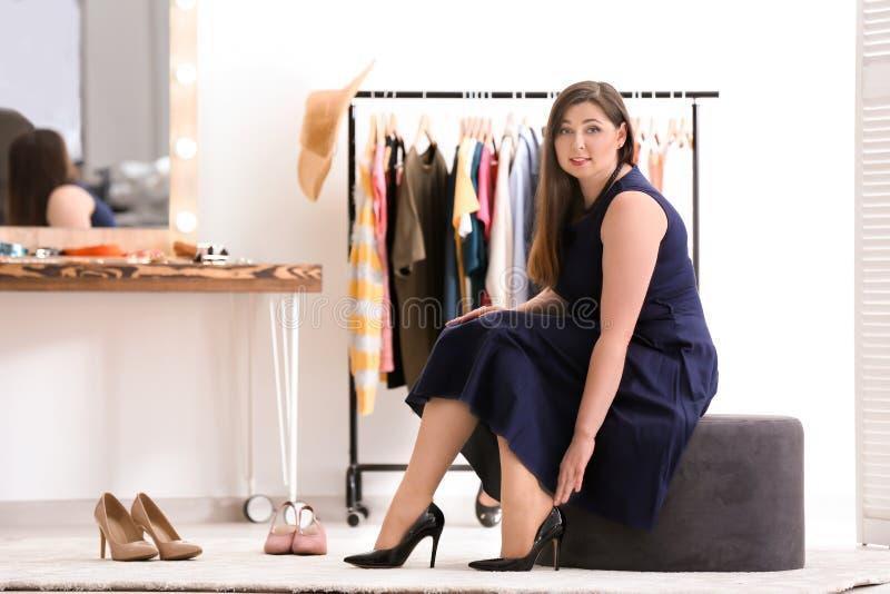 Schöne überladene Frau, die auf Schuhen versucht stockbilder