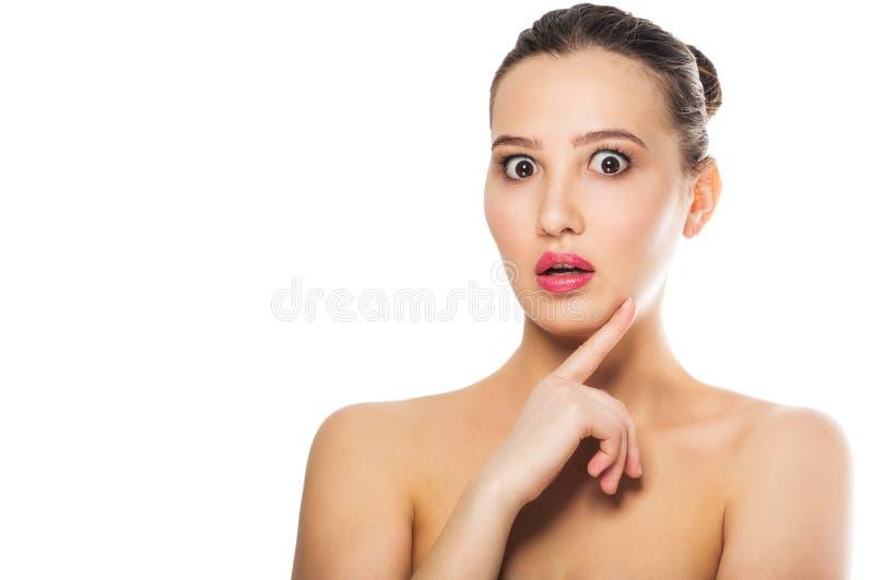 Schöne überraschte Brunettefrau auf weißem Isolathintergrund Ausdrucksvolle Gesichtsausdrücke Cosmetology, Badekurort stockfoto