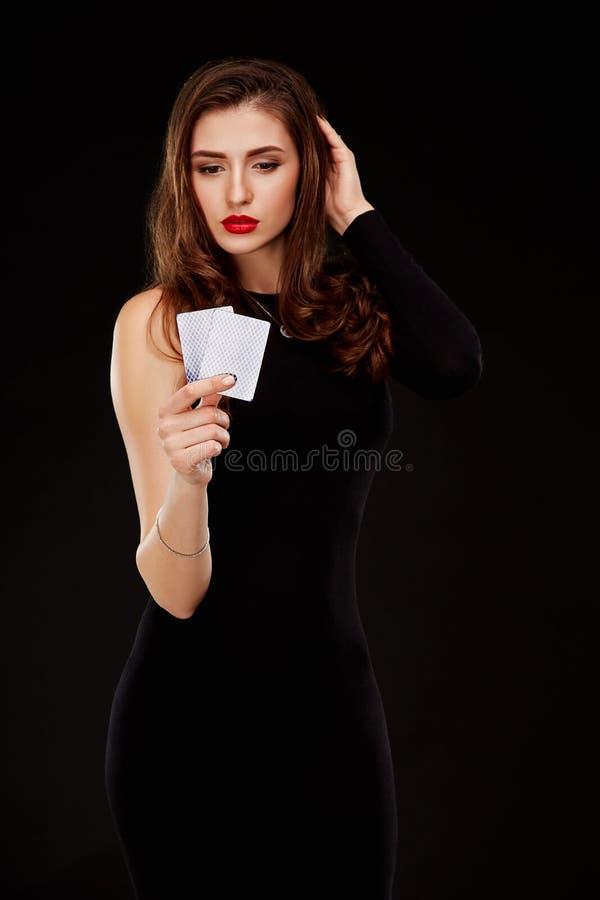 Schöne überzeugte Frau, die Pokerkarten mit Kopienplatz zeigt und betrachtet lizenzfreie stockfotos