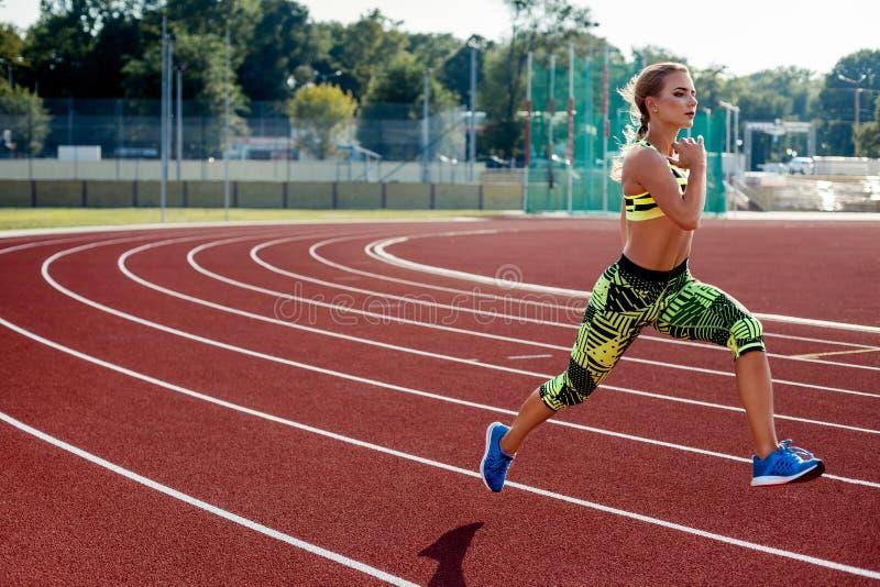 Schöne Übung der jungen Frau, die auf athletischer Bahn auf Stadion rüttelt und läuft stockbilder