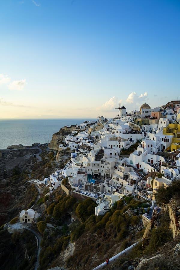 Schöne Abendlichtszene weißen Gebäude Oia townscape, das entlang Inselberg, weitem Ozean, weicher Wolke und blauem Himmel mischt lizenzfreies stockbild
