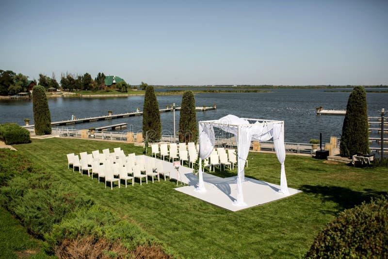 Schöne abgehende Heiratseinrichtung Jüdisches Hupa auf romantischer Heiratszeremonie, Hochzeit im Freien auf der Rasenwasseransic lizenzfreie stockfotografie