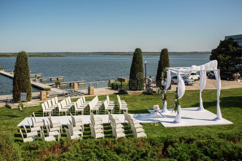 Schöne abgehende Heiratseinrichtung Jüdisches Hupa auf romantischer Heiratszeremonie, Hochzeit im Freien auf der Rasenwasseransic lizenzfreies stockbild
