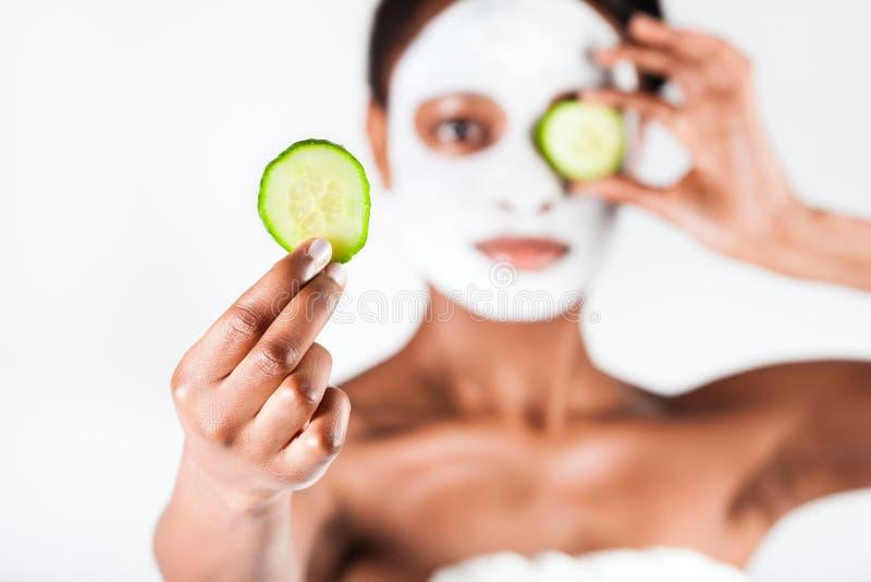 Schöne Afrikanerin im Studio mit Gesichtsmaske lizenzfreies stockbild