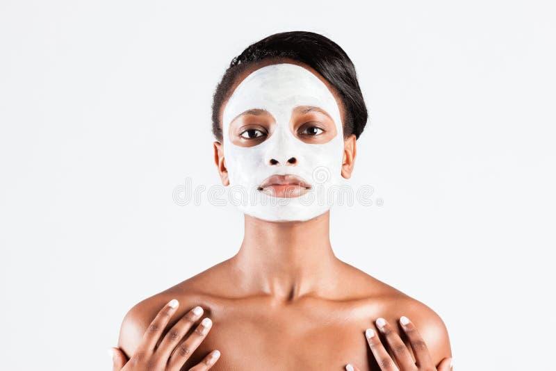 Schöne Afrikanerin im Studio mit Gesichtsmaske lizenzfreie stockfotografie