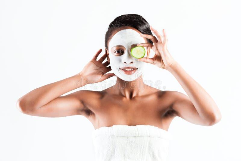 Schöne Afrikanerin im Studio mit Gesichtsmaske stockbild
