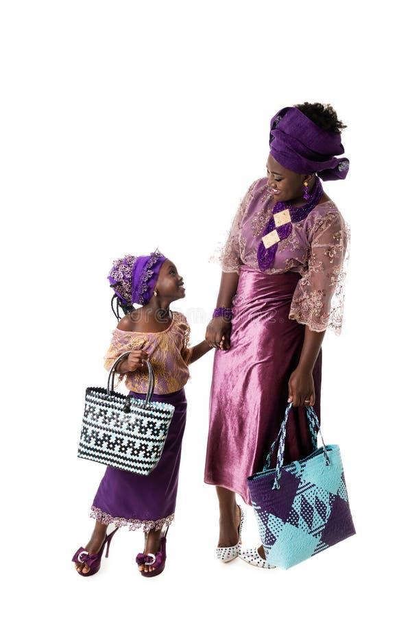 Schöne Afrikanerin und reizendes kleines Mädchen in der traditionellen purpurroten Kleidung, lokalisiert stockfotografie
