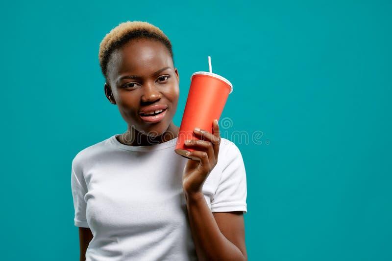Schöne afrikanische Frau, die rote Papierschale hält und zeigt lizenzfreies stockbild