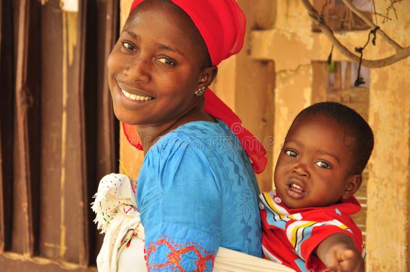 Schöne afrikanische Frau mit Schätzchen lizenzfreie stockbilder