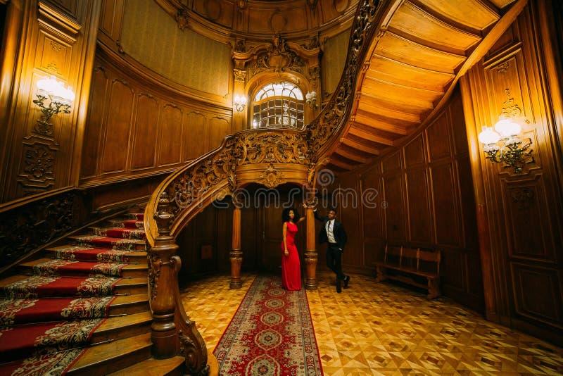 Schöne afrikanische Paare, die an der Weinlesetreppe aufwerfen Luxuriöser Theaterinnenraumhintergrund lizenzfreie stockfotos
