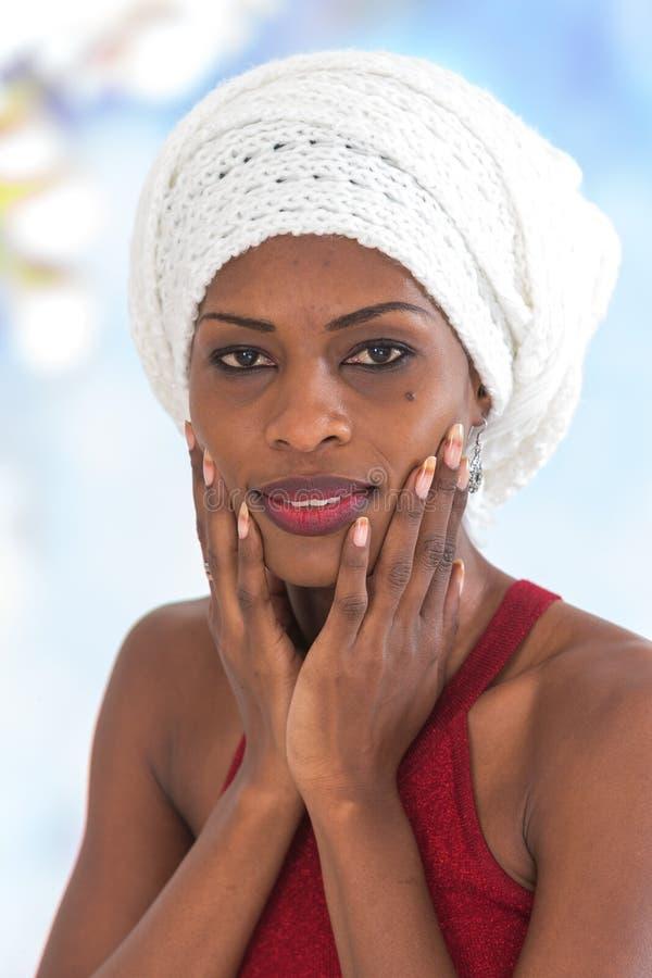 Schöne afro-amerikanische Frau, die einen traditionellen Hirsekornschal trägt lizenzfreie stockfotos