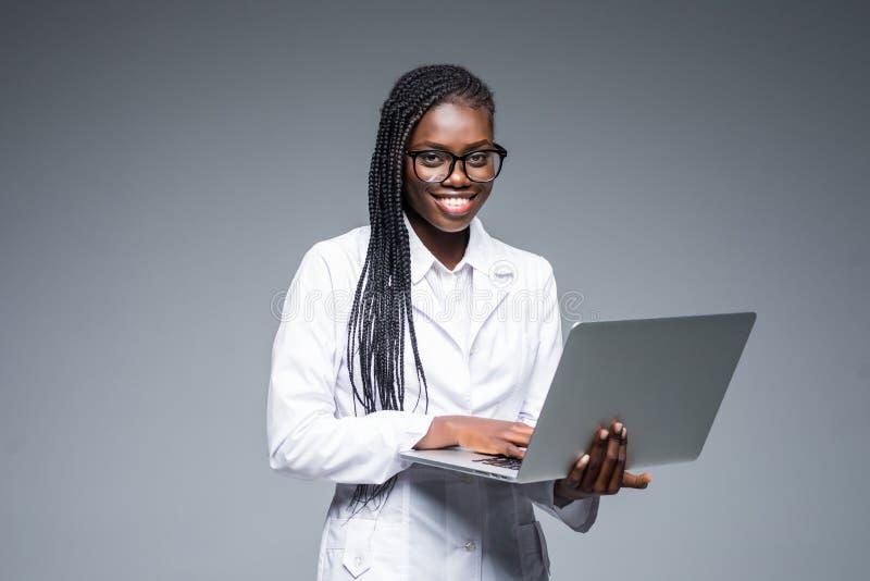 Schöne Afroamerikanerärztin oder -krankenschwester, die eine Laptop-Computer lokalisiert auf einem grauen Hintergrund hält stockbild