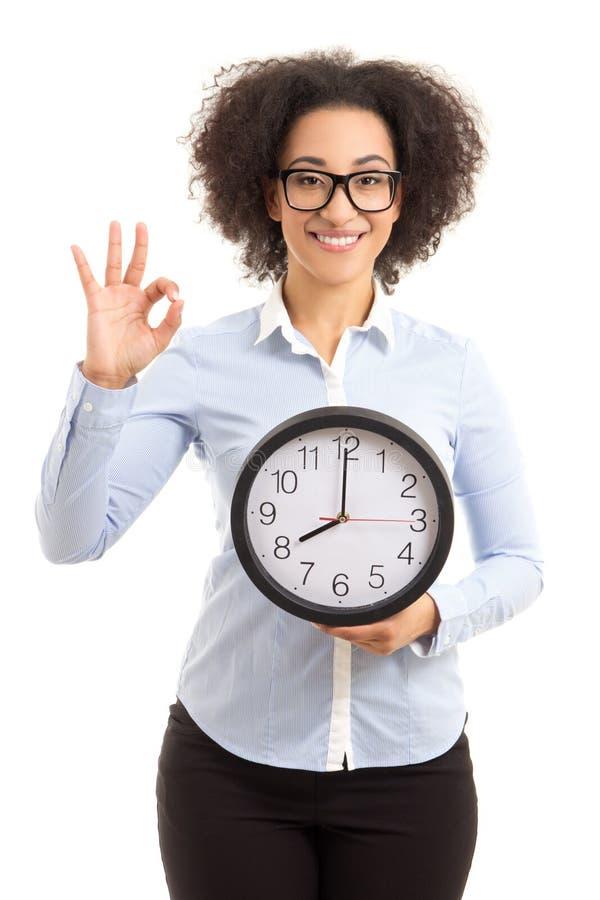 Schöne Afroamerikanerfrau, die Büro Uhr und showin hält stockfotos