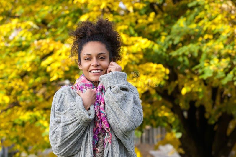 Schöne Afroamerikanerfrau, die im Herbst lächelt lizenzfreie stockfotos