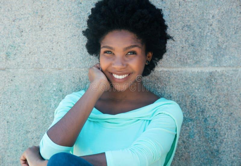Schöne Afroamerikanerfrau in einem hellgrünen Hemd stockbild