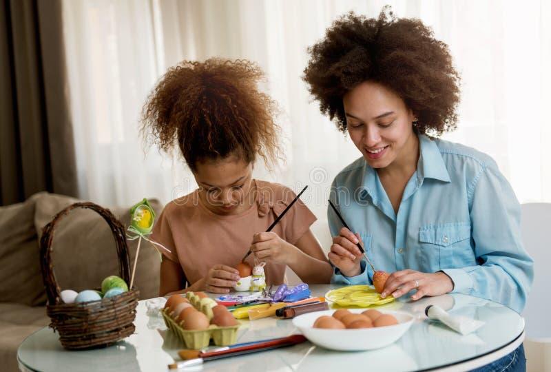 Schöne Afroamerikanerfrau und ihre Tochter, die Ostereier färbt lizenzfreie stockbilder