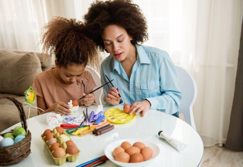 Schöne Afroamerikanerfrau und ihre Tochter, die Ostereier färbt stockfoto
