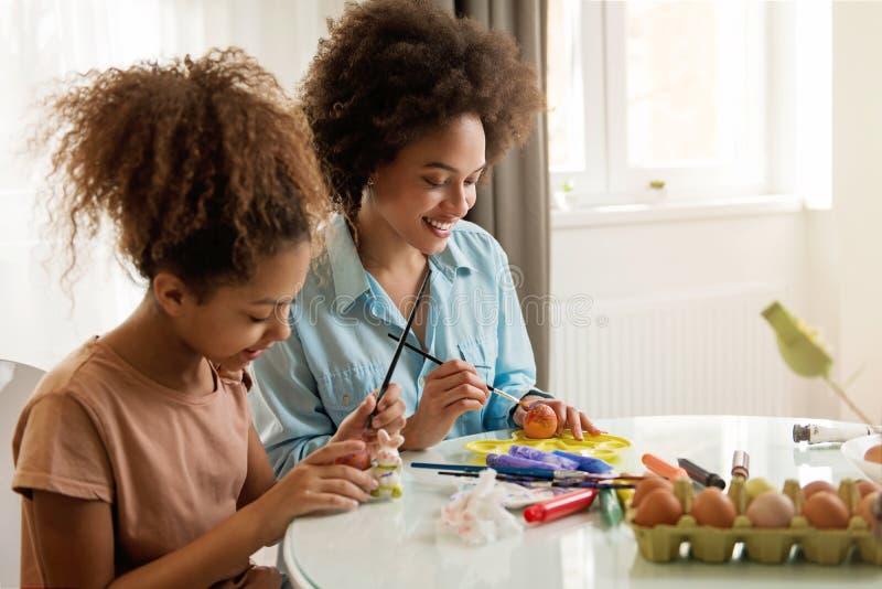 Schöne Afroamerikanerfrau und ihre Tochter, die Ostereier färbt lizenzfreies stockfoto