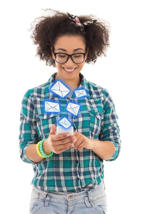 Schöne Afroamerikanerjugendliche, die sms Mitteilungsesprit sendet stockfotos