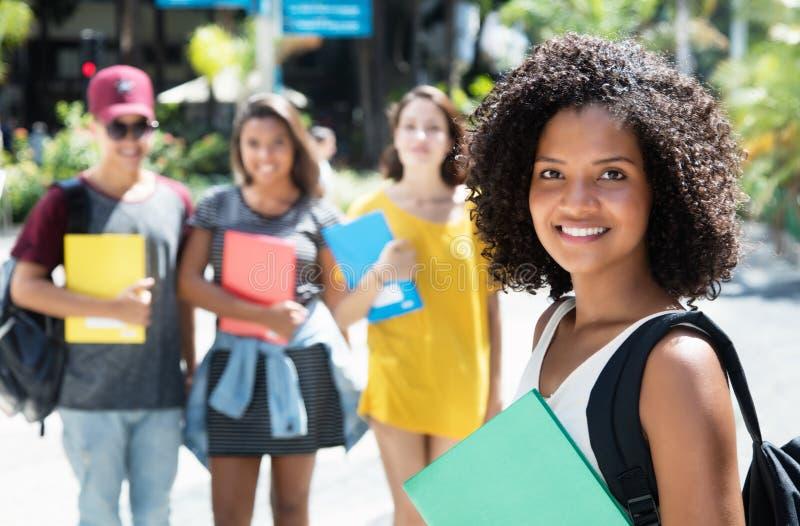 Schöne Afroamerikanerstudentin mit Gruppe internat stockbild