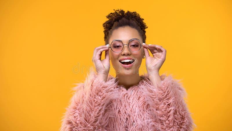 Schöne afroe-amerikanisch Frau, die auf neue rosa Gläser, Modeindustrie sich setzt lizenzfreies stockfoto