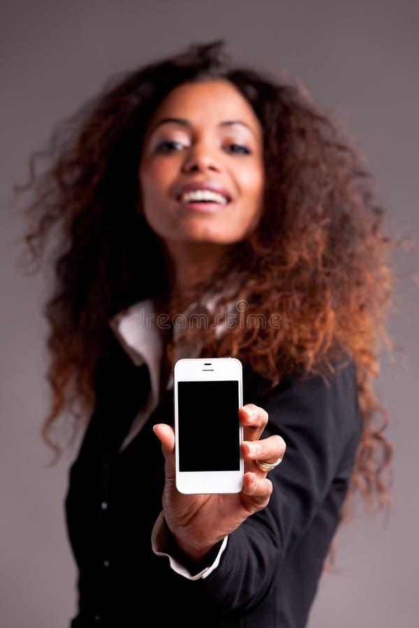 Schöne afroe-amerikanisch Frau, die Telefon zeigt lizenzfreies stockbild